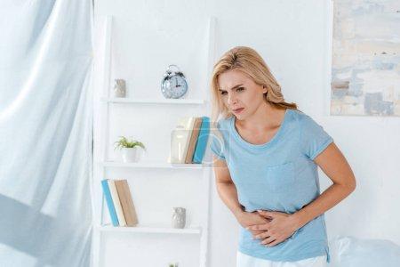 Photo pour Femme malade ayant mal au ventre à la maison - image libre de droit