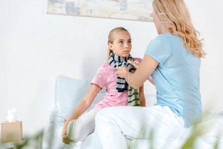 Photo pour Foyer sélectif de la mère touchant écharpe rayée de fille malade - image libre de droit