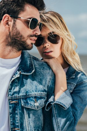 Photo for Attractive woman and handsome man in denim jackets hugging outside - Royalty Free Image