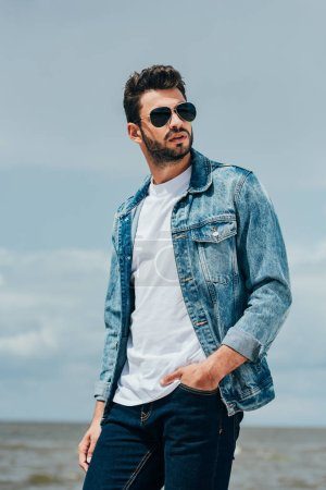 Photo for Handsome man in denim jacket and sunglasses looking away - Royalty Free Image