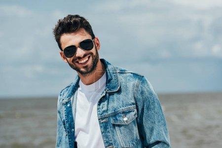 Photo pour Bel homme en jean veste et lunettes de soleil en regardant la caméra - image libre de droit