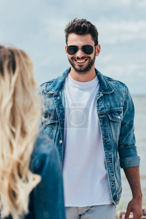 Photo for Selective focus of handsome man in denim jacket smiling and looking at woman - Royalty Free Image