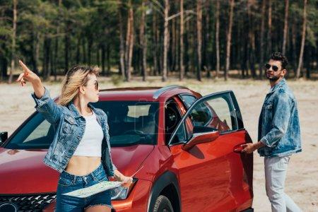 Photo pour Attrayant femme tenant carte et parler avec bel homme en veste - image libre de droit