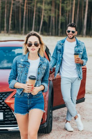 Photo for Attractive woman and handsome man in denim jackets holding paper cups - Royalty Free Image
