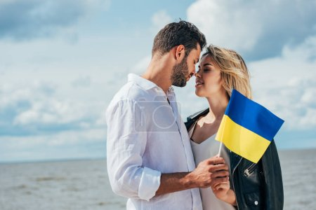 Photo pour Femme attirante et bebeau homme retenant le drapeau ukrainien à l'extérieur - image libre de droit
