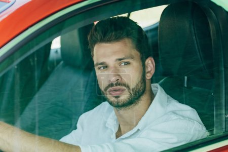 Photo for Handsome man in white shirt driving car and looking away - Royalty Free Image