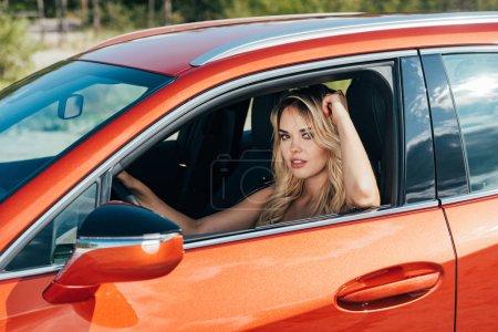 Photo pour Femme attirante et blonde s'asseyant dans la voiture et regardant l'appareil-photo - image libre de droit