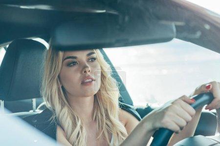 attraktive und blonde Frau sitzt im Auto und schaut weg
