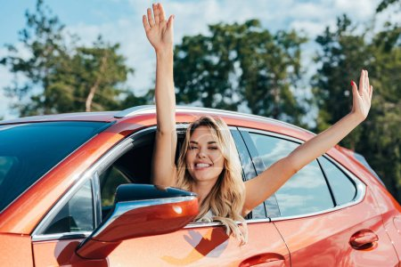 Photo for Attractive and blonde woman sitting in car and looking at camera - Royalty Free Image