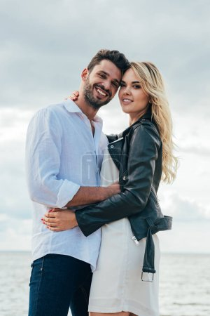 Photo for Attractive woman and handsome man smiling and hugging outside - Royalty Free Image