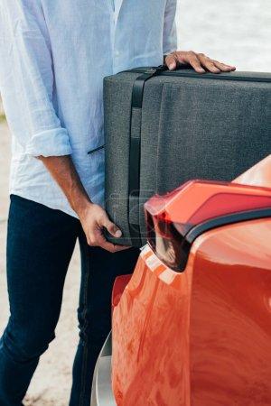 Photo pour Vue recadrée de l'homme en chemise mettant valise en voiture - image libre de droit