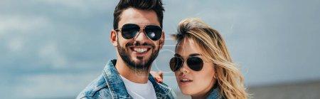 Photo pour Tir panoramique de la femme attirante et de l'homme beau dans des lunettes de soleil souriant à l'extérieur - image libre de droit