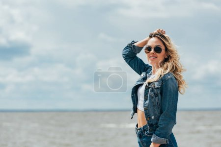 Photo for Blonde and attractive woman in denim jacket and sunglasses looking away - Royalty Free Image