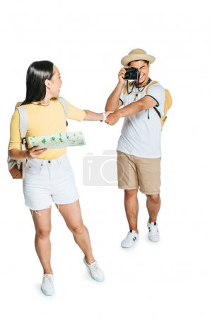 Photo for Young asian tourist taking photo of girlfriend holding map on white background - Royalty Free Image