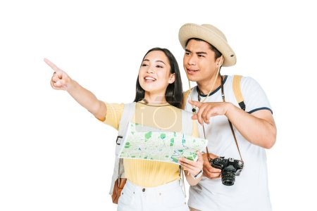 two cheerful asian tourists pointing with fingers while holding map isolated on white
