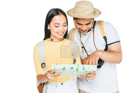 Photo for Two young asian tourists smiling while looking at map isolated on white - Royalty Free Image