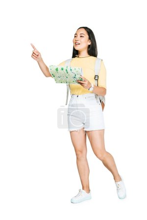 attractive asian girl looking away and pointing with finger while holding map on white background
