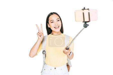 Photo pour Attrayant asiatique femme montrant signe de victoire tout en prenant selfie sur smartphone avec selfie bâton isolé sur blanc - image libre de droit