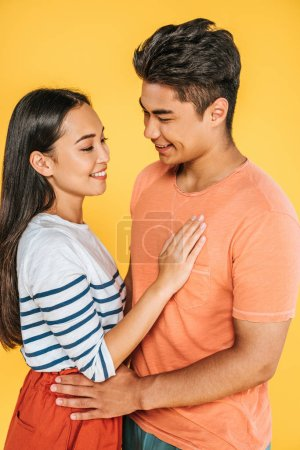 Photo for Happy asian man and woman hugging while looking at each other isolated on yellow - Royalty Free Image