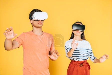 jeune homme et femme geste tout en utilisant des casques de réalité virtuelle sur fond jaune