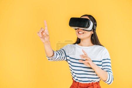 souriant fille geste tout en utilisant la réalité virtuelle casque isolé sur jaune