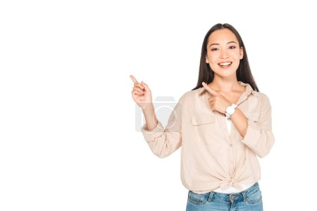 Photo for Cheerful asian woman pointing with fingers while looking at camera isolated on white - Royalty Free Image