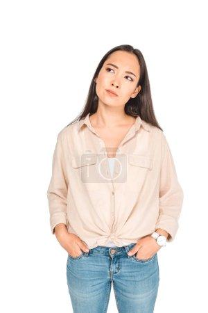 Photo pour Réfléchie asiatique femme tenant la main dans les poches tout en regardant loin isolé sur blanc - image libre de droit