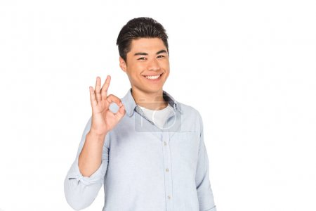 Photo for Happy asian man showing okay sign while smiling at camera isolated on white - Royalty Free Image