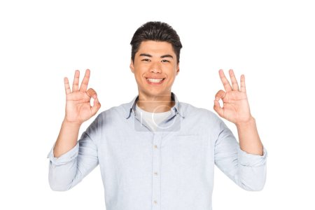 cheerful asian man showing okay signs while smiling at camera isolated on white