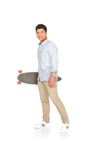 Photo for Handsome asian man holding longboard while looking at camera on white background - Royalty Free Image