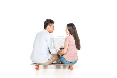 Photo for Happy asian couple sitting on longboard and looking at each other on white background - Royalty Free Image