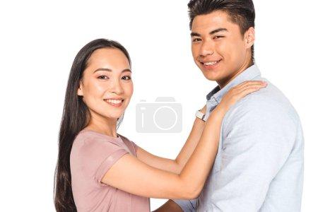 Photo pour Heureux asiatique femme tenant mains sur épaules de sourire copain tout en regardant caméra isolé sur blanc - image libre de droit