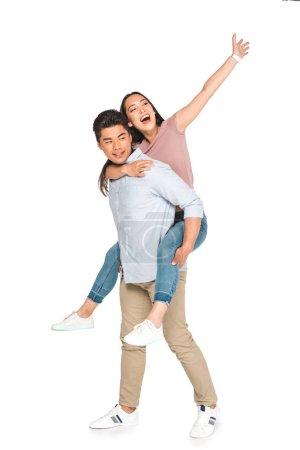 Foto de Alegre mujer asiática agitando la mano mientras piggybacking en el novio feliz sobre fondo blanco - Imagen libre de derechos