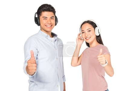 smiling asian man and woman showing thumbs up while listening music in headphone and looking at camera isolated on white