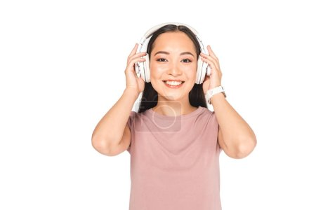 Photo for Attractive asian girl smiling at camera while listening music in headphones isolated on white - Royalty Free Image
