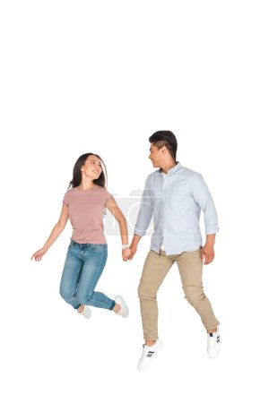 Photo for Happy asian man and woman jumping while holding hands on white background - Royalty Free Image