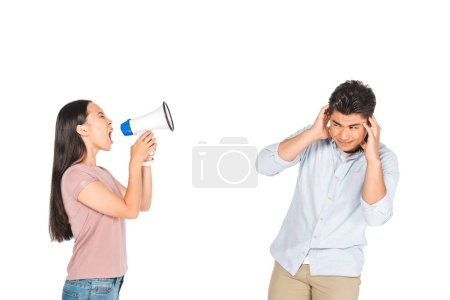 Photo for Angry asian girl screaming into megaphone at boyfriend covering ears with hands isolated on white - Royalty Free Image