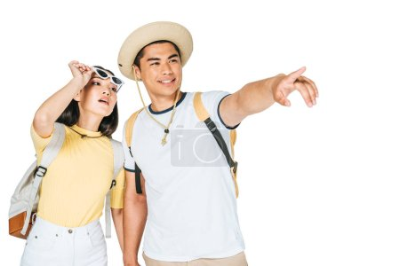 handsome asian man pointing with finger while holding hands with pretty girlfriend isolated on white