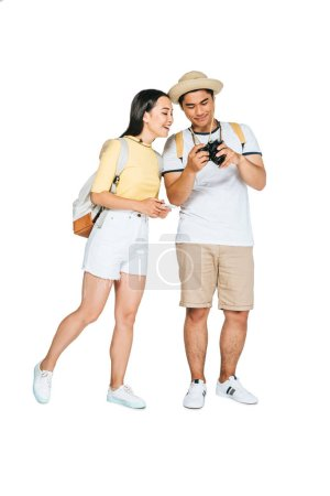 Photo for Cheerful asian man showing digital camera to smiling girlfriend on white background - Royalty Free Image