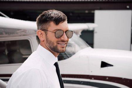 Photo pour Bearded pilot in formal wear and sunglasses smiling near plane - image libre de droit