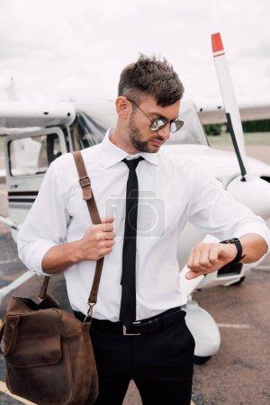 Foto de Piloto barbudo en gafas de sol de pie cerca del avión y mirando el reloj de pulsera - Imagen libre de derechos