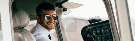 Photo pour Prise de vue panoramique du beau pilote souriant dans les lunettes de soleil en regardant la caméra dans l'avion - image libre de droit