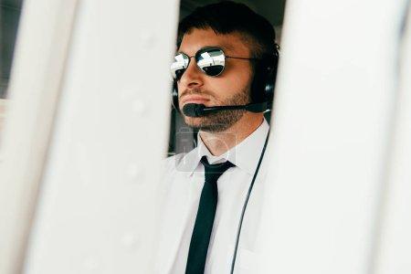 Photo pour Pilote sérieux dans les lunettes de soleil et le casque regardant loin - image libre de droit