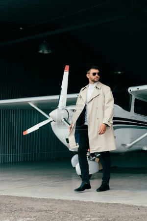 Photo for Full length view of stylish businessman in coat standing near plane - Royalty Free Image