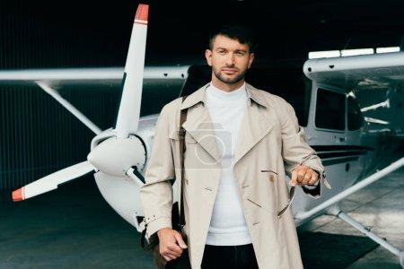Foto de Pensativo hombre de negocios con abrigo de pie cerca del avión - Imagen libre de derechos