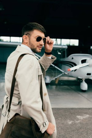 Photo for Pensive stylish businessman in coat standing near plane - Royalty Free Image