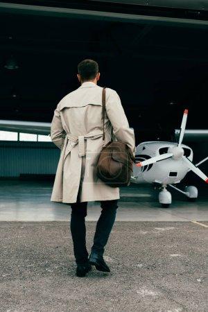 Photo pour Vue arrière de l'homme d'affaires élégant dans le manteau restant près de l'avion - image libre de droit