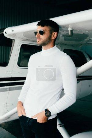 Photo pour Beau jeune homme en tenue décontractée debout avec les mains dans les poches près de l'avion et regardant loin - image libre de droit