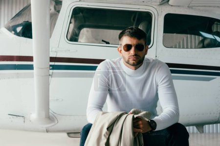 Photo for Front view of man in sunglasses and casual attire sitting near plane - Royalty Free Image