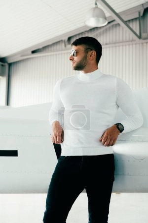 Photo for Pensive man in sunglasses standing near plane and looking away - Royalty Free Image